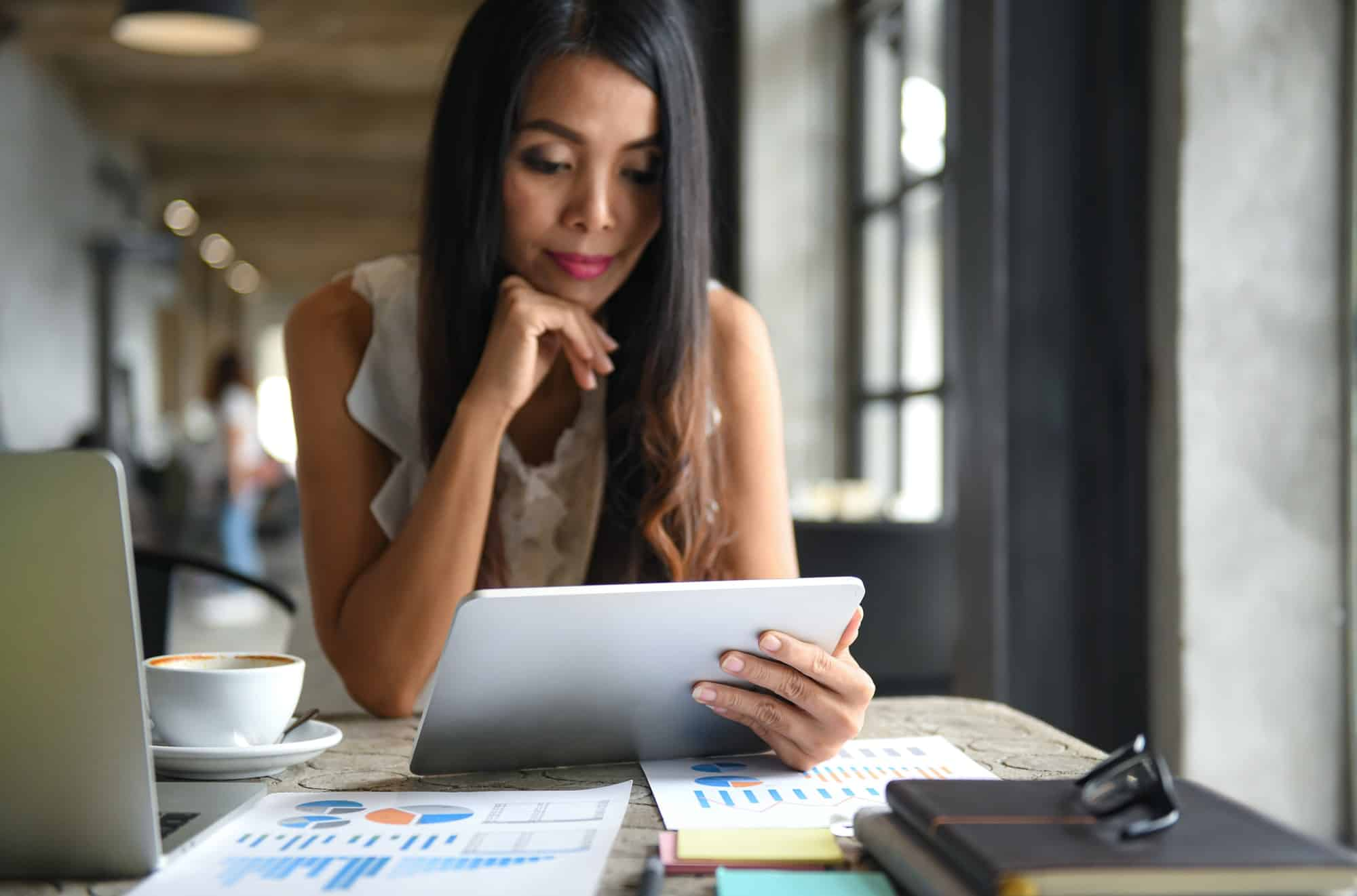 Mulher usando o tablet para ler documentos eletrônicos